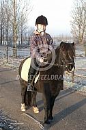 Meisje op pony in de winter